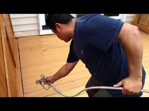 Spraying natural sealer to a deck