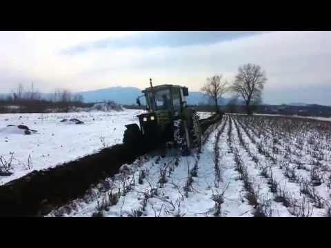 Plowing in a snow with tractor Hurlimann H-488 Prestige