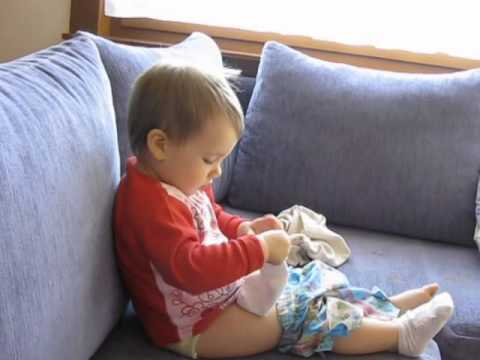 A funny 2-year-old girl dressing herself,