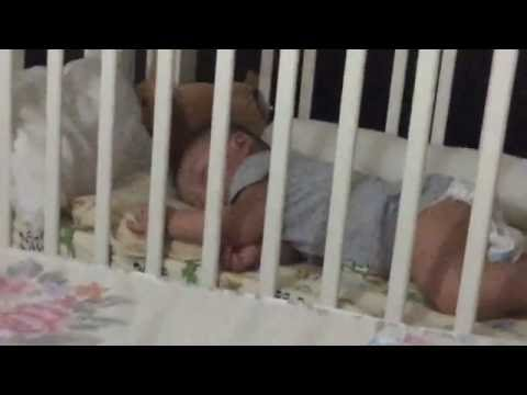 Baby sleeping in crib and dady nose lol