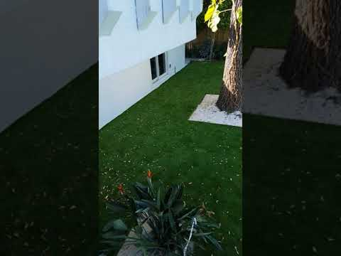 Artificial grass installation on balcony for home in Miami. Artificial ivy wall installation.