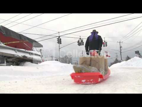 NY SNOW: MAN USES SLED TO CARRY GROCERIES