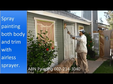 Painting the exterior of a house with spray gun.