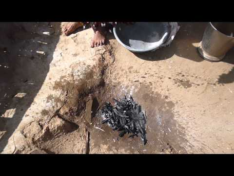 Sprinkling water onto charcoal to stop it from turning into ash