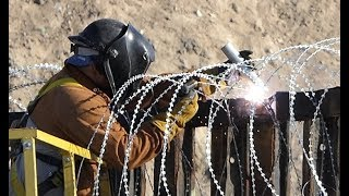 ON LOCATION AT THE BORDER: BORDER PATROL REINFORCING BORDER FENCE WITH RAZOR WIRE