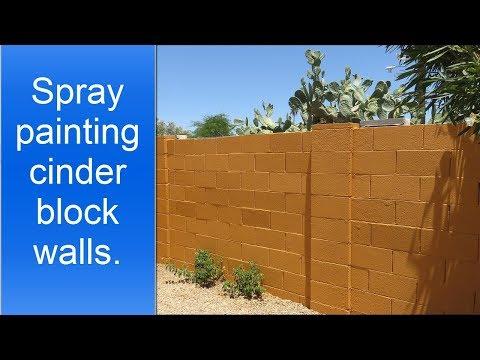 Spray painting exterior cinder block walls.