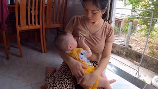Mom Thuy is breastfeeding at home as daily routine for baby while she is doing cooking...