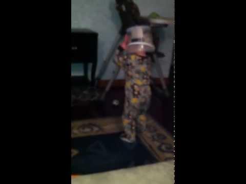 Eli walking with a bucket on his head