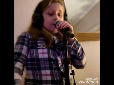 Girl aged 9 singing into microphone (Cake by the ocean)