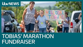 'Captain' Tobias, nine, completes marathon using a walker raising thousands for charity | ITV News