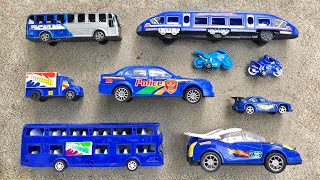 Find blue toy vehicles in the sand, Double Decker Bus, Police Car, City Bus, Sports Bike
