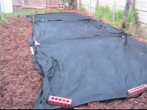 Laying down landscape fabric in garden