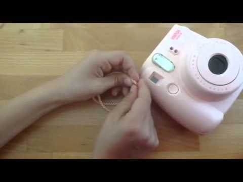 How to attach the wrist strap of a Polaroid mini camera