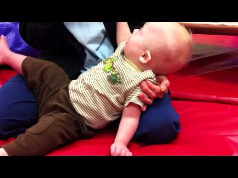 Baby with Down Syndrome learning to crawl at physical therapy