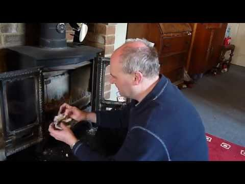 how to clean the tar off the glass of a wood burning stove using ash