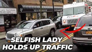 Selfish lady holds up traffic for 2 blocks because she won't move her double parked car