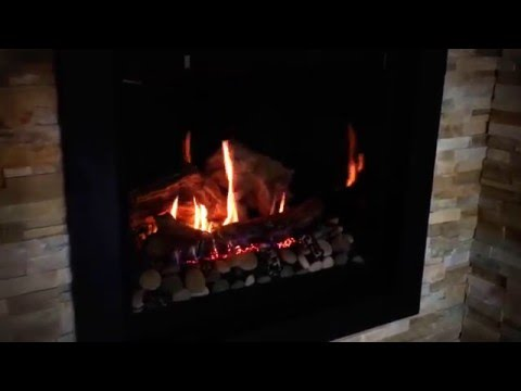 Marquis Bentley Gas Fireplace with driftwood and river rocks available at Safe Home Fireplace