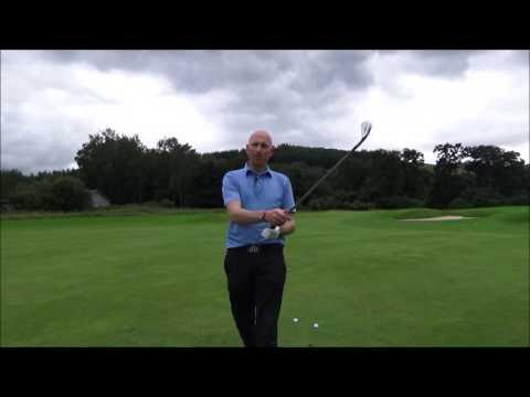 How do I hit the golf ball lower