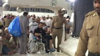 Touching the black stone (Hajr e Aswad) by the Kaaba in a wheelchair