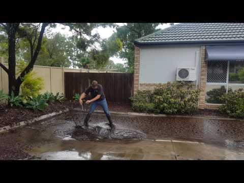 Plumber clearing a blocked grate after storm