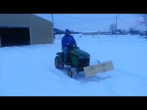 Plowing snow with homemade snow plow for lawnmower