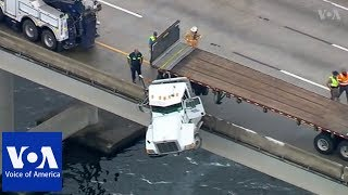 Front of truck dangles off bridge in southern US