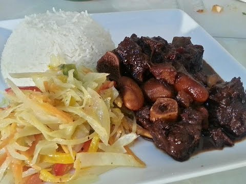 One Of The Best Jamaican Oxtail Recipes Served With Plain Rice And Stir Fry Cabbage
