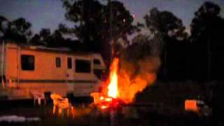 Guy throws propane tank in fire.