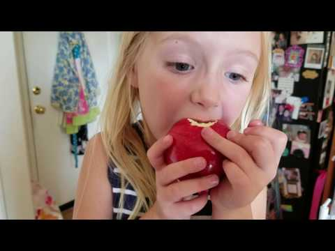 Ella tries to pull loose tooth by eating apple