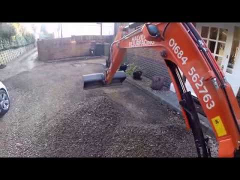 Mini Excavator Removing Gravel Off A Driveway