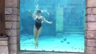 Female diver underwater performs cool tricks underwater