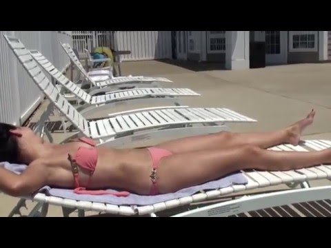Sexy hot girl at the swimming pool laying out