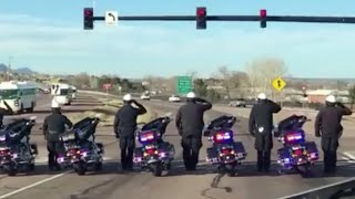 Police officers salute soldiers returning home from Afghanistan