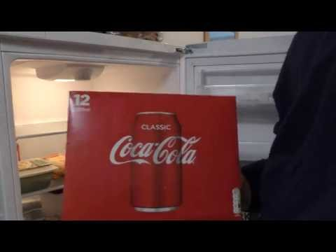 Few seconds to unload 12 pack Coca Cola cans into a fridge