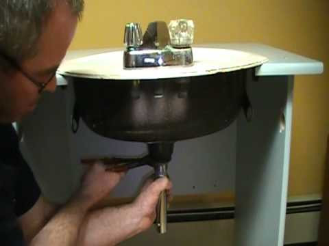 Old plumber shows how to install a drain on a bathroom sink (basin).Mechanical P.O.plug
