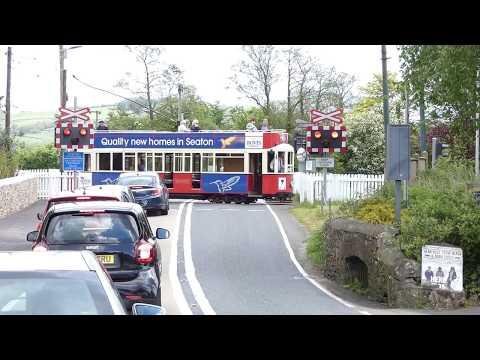 Seaton Tramway tram crosses main road at Colyford Dorset England UK