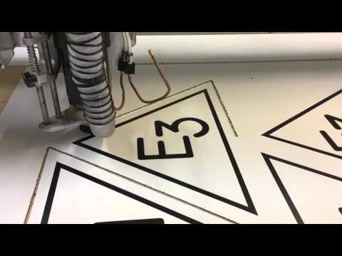 Signs being router cut out of aluminum composite on a Multicam 3000