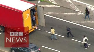 Moment Calais migrants jumped onboard lorries - BBC News