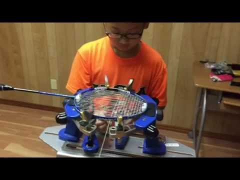 A 10 year-old boy shows how to string a badminton racket