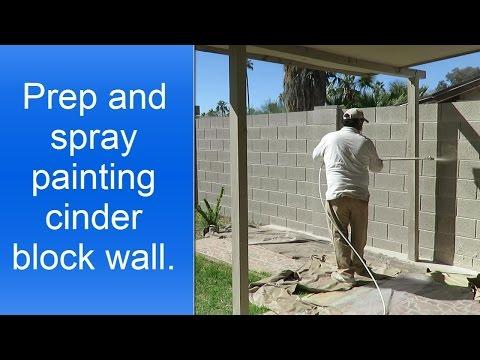 Spray painting cinder block wall.