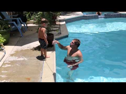 Austin jumps into the pool during his private swimming lesson