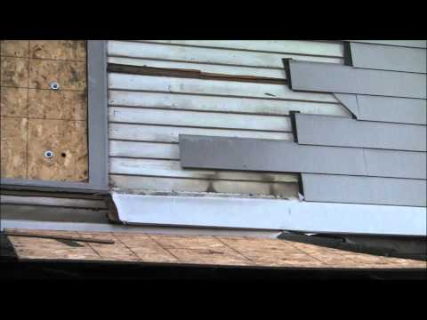 Removing old asbestos clapboard siding by duct taping a flat prybar to an extendable painting rod