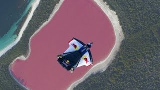 Wingsuit flying over a pink lake in Australia