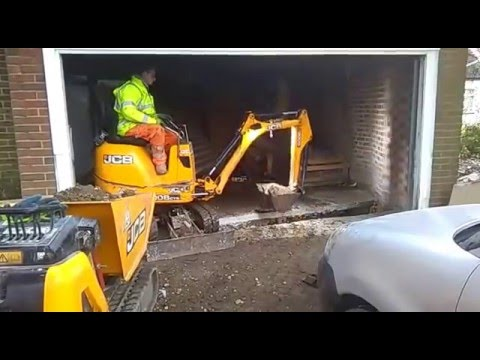 DMS micro digger hire. JCB Micro digger working inside a garage.