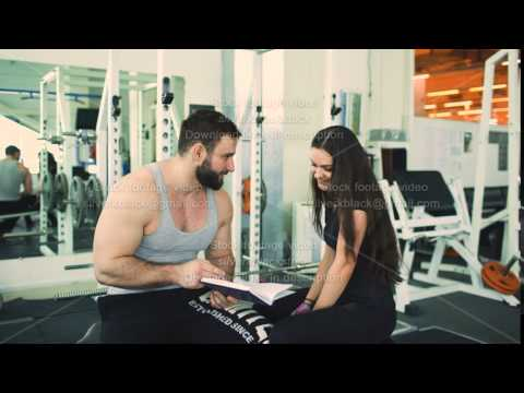 Trainer helps young strong brunette woman write training program in fitness club and gym center