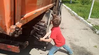 Мальчик 8-ми лет управляет гидравликой мусоровоза.