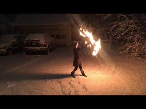Lady Blaze spins fire fans in a snowstorm
