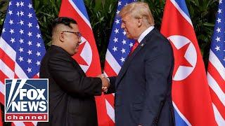 Trump and Kim Jong Un begin summit with groundbreaking handshake