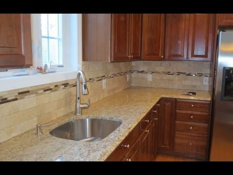 Travertine subway tile kitchen backsplash with a mosaic glass tile border