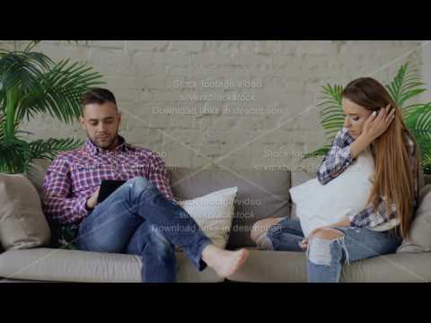 Young upset woman is stressed and unhappy while her boyfriend using tablet computer sit on couch at